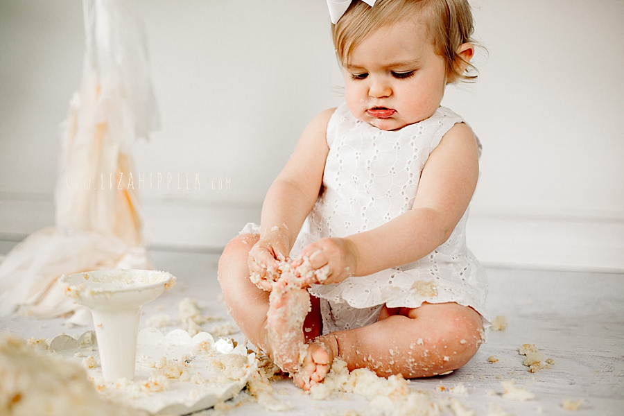 one year old girl in white dress played with cake-filled toes