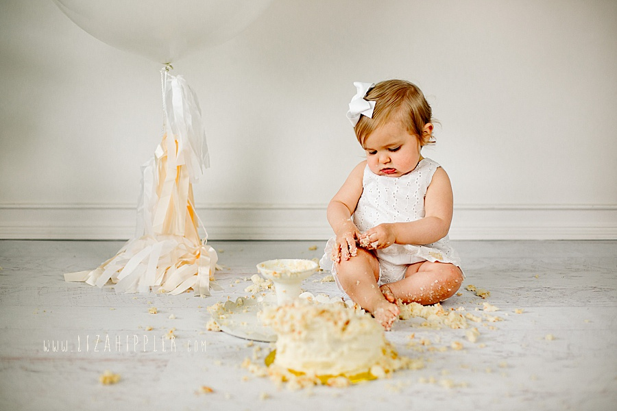 cake smash session for one year old girl with neutral colors