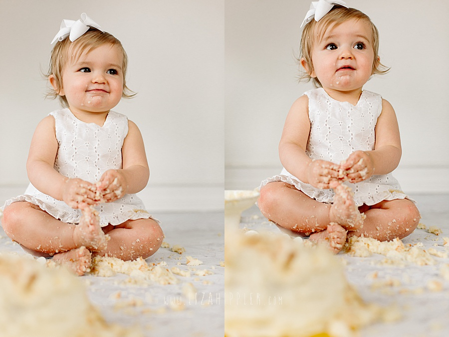 adorable one year old girl with blonde hair and white dress sits in cake