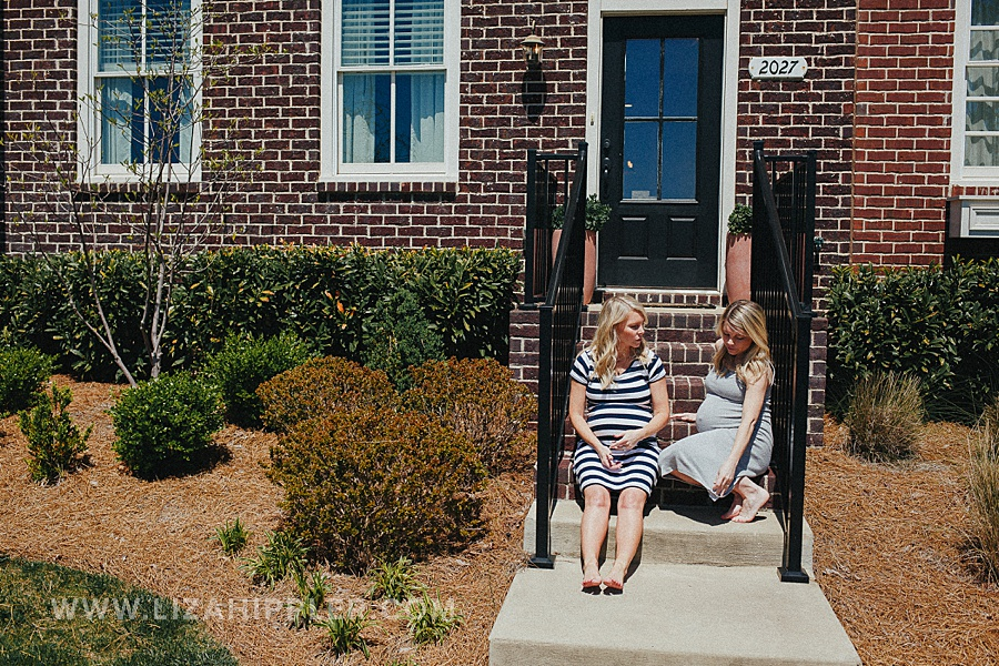 pregnant sisters sit on front stoop steps