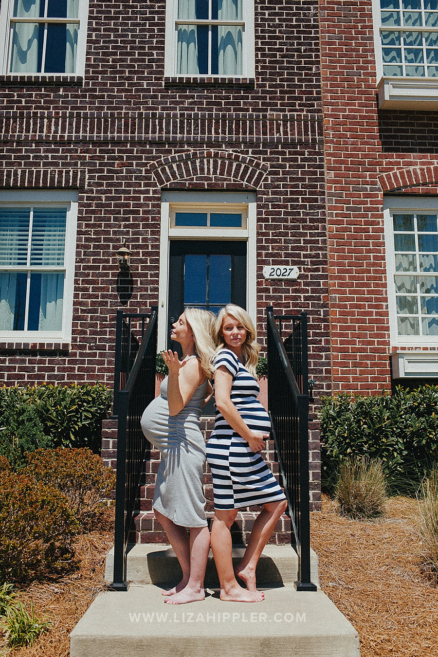 maternity shoot of pregnant sisters standing back-to-back