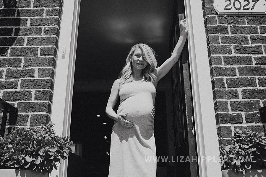 maternity shoot of pregnant woman in her doorframe