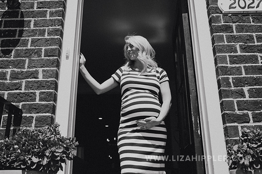 pregnant woman in striped dress in doorframe