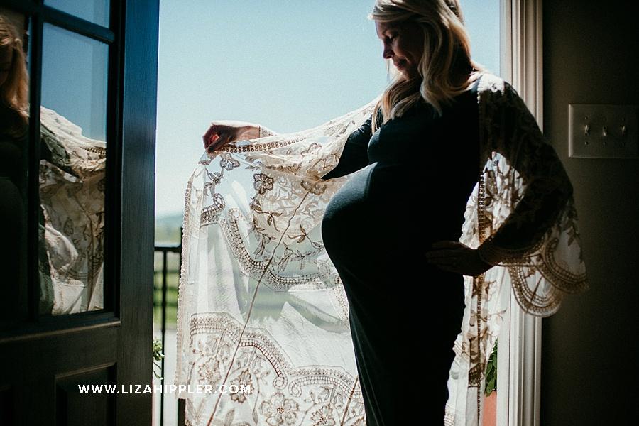 maternity photoshoot of woman wearing tight black dress and lace kimono