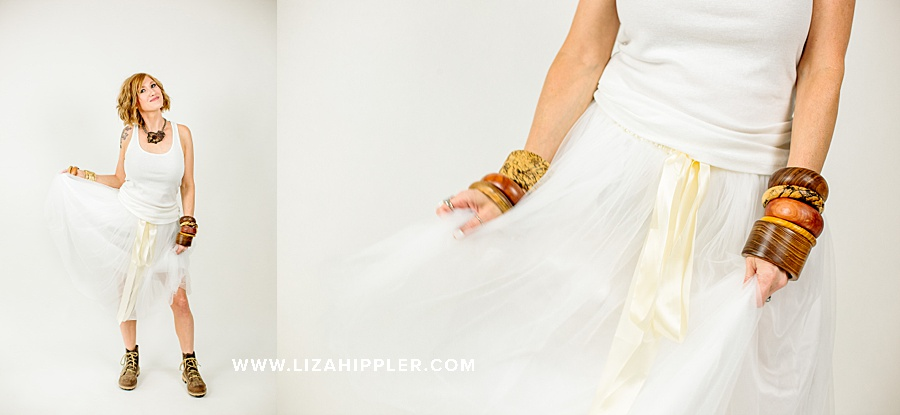 jewelry maker shows off wooden jewelry while wearing white tulle skirt