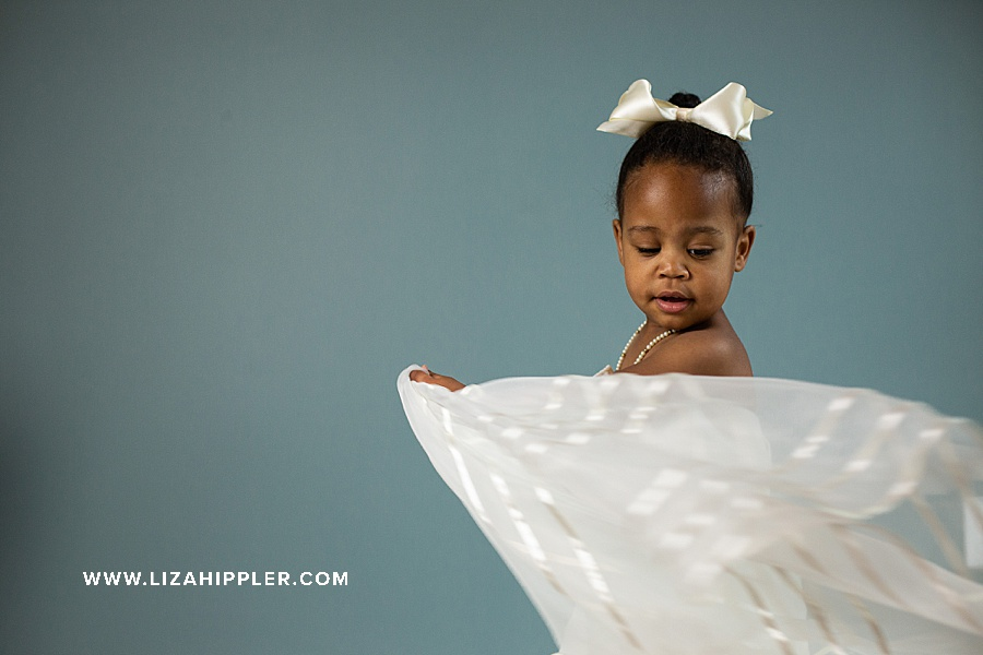 two year old spins in mom's wedding dress for birthday photoshoot