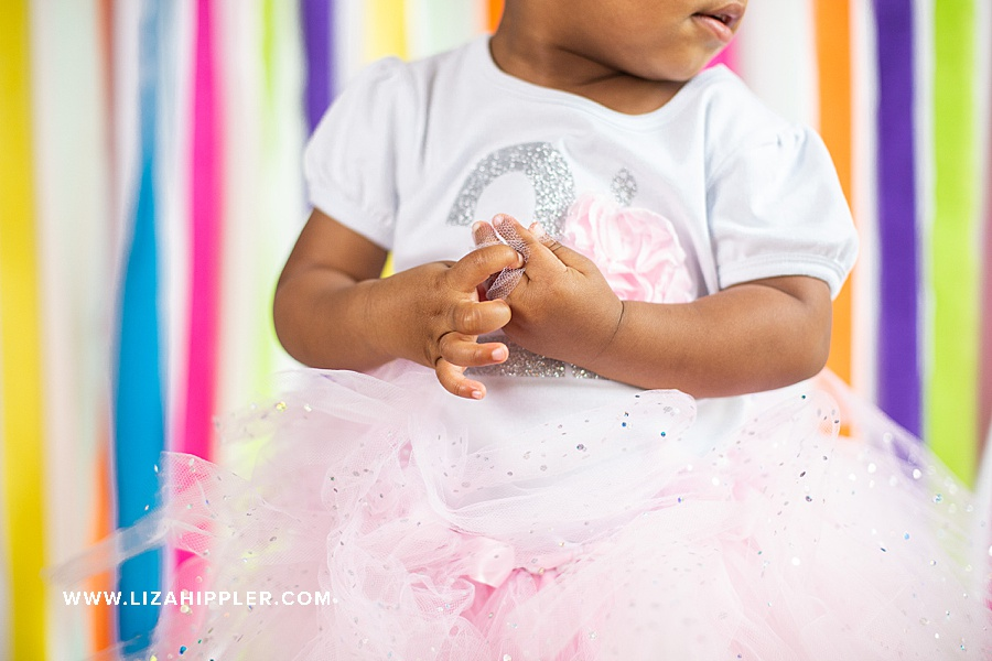 close up of 2 year old hands holding  a tutu for birthday photos