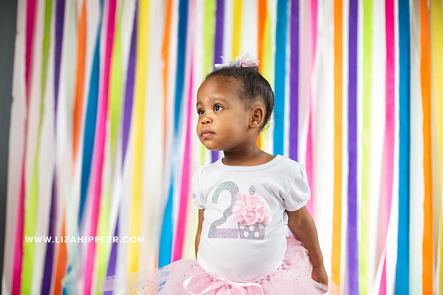 2nd birthday photo of girl in tutu dress with colorful streamer background