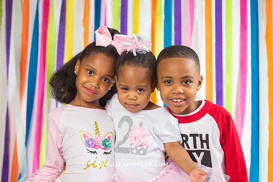three african american siblings smile for their birthday photoshoot with colorful background