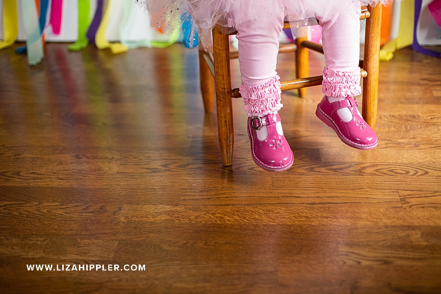pink shoes of little girl sitting on chair