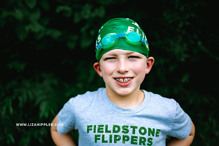 boy in swim cap smiles with braces