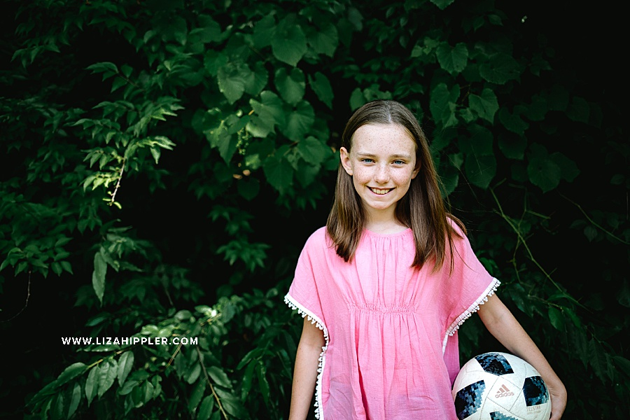 girl in pink shirt holds soccer ball