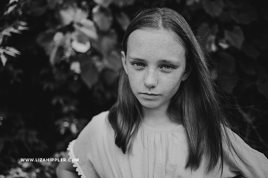 black and white image close up of girl with freckles
