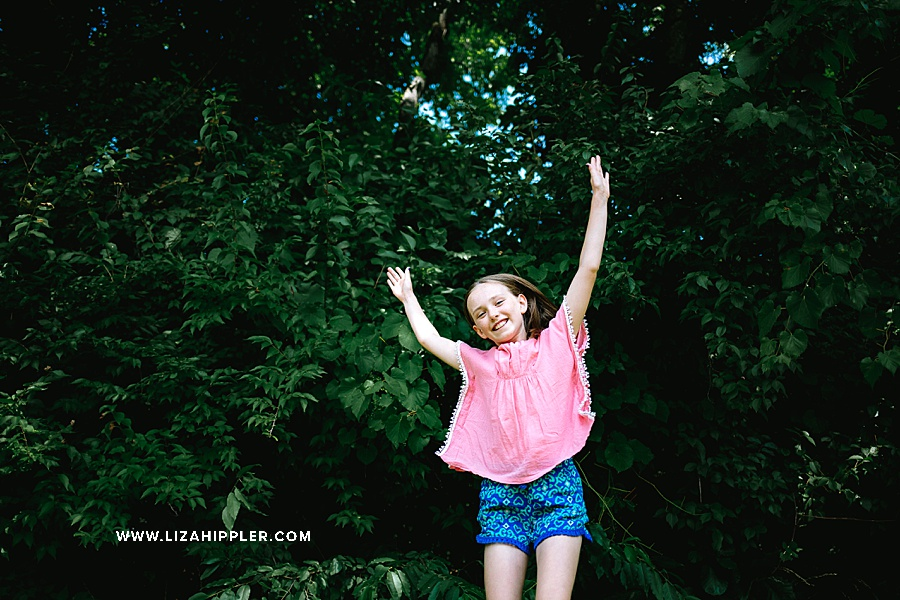 girl in pink dress jumps for joy