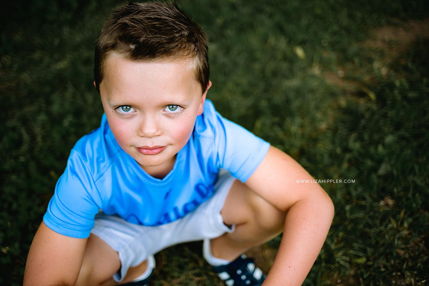 blue-eyed boy looks up at camera