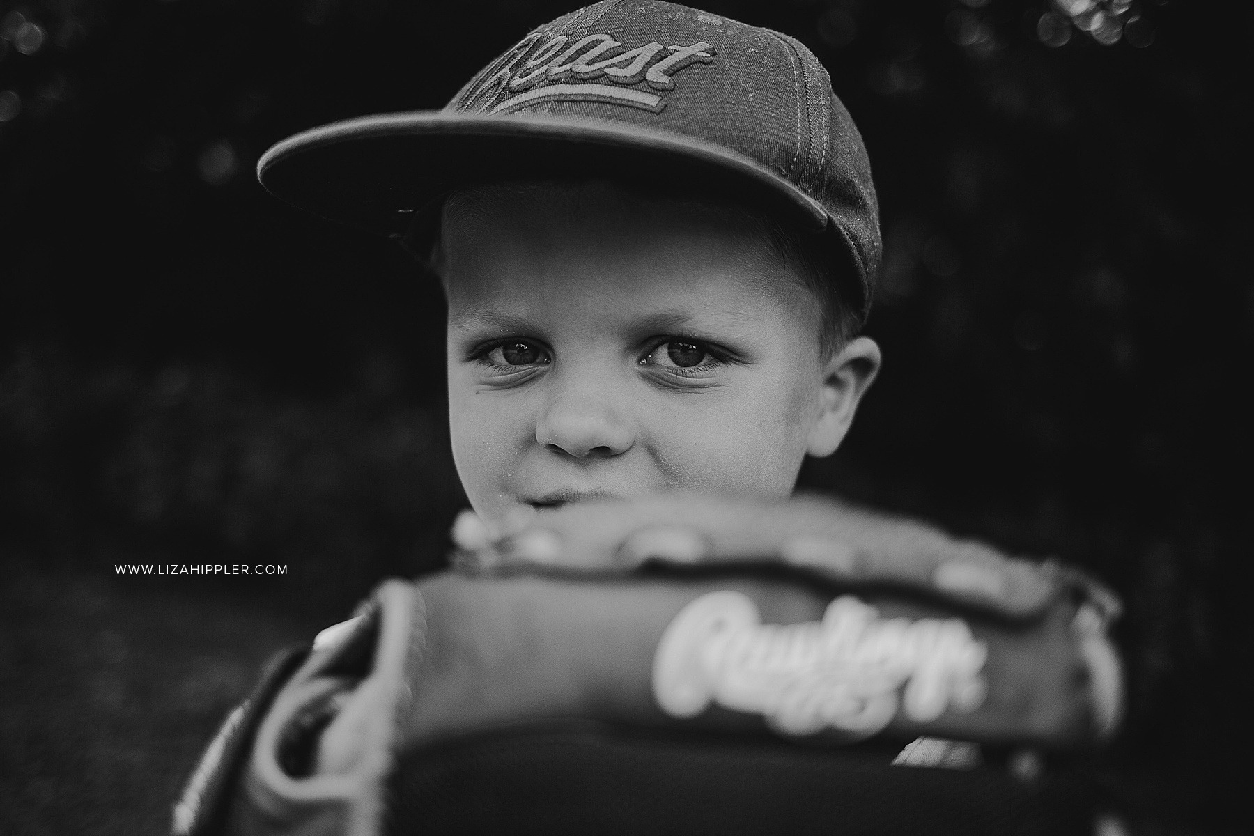 black and white image of close-up of boy with baseball mitt