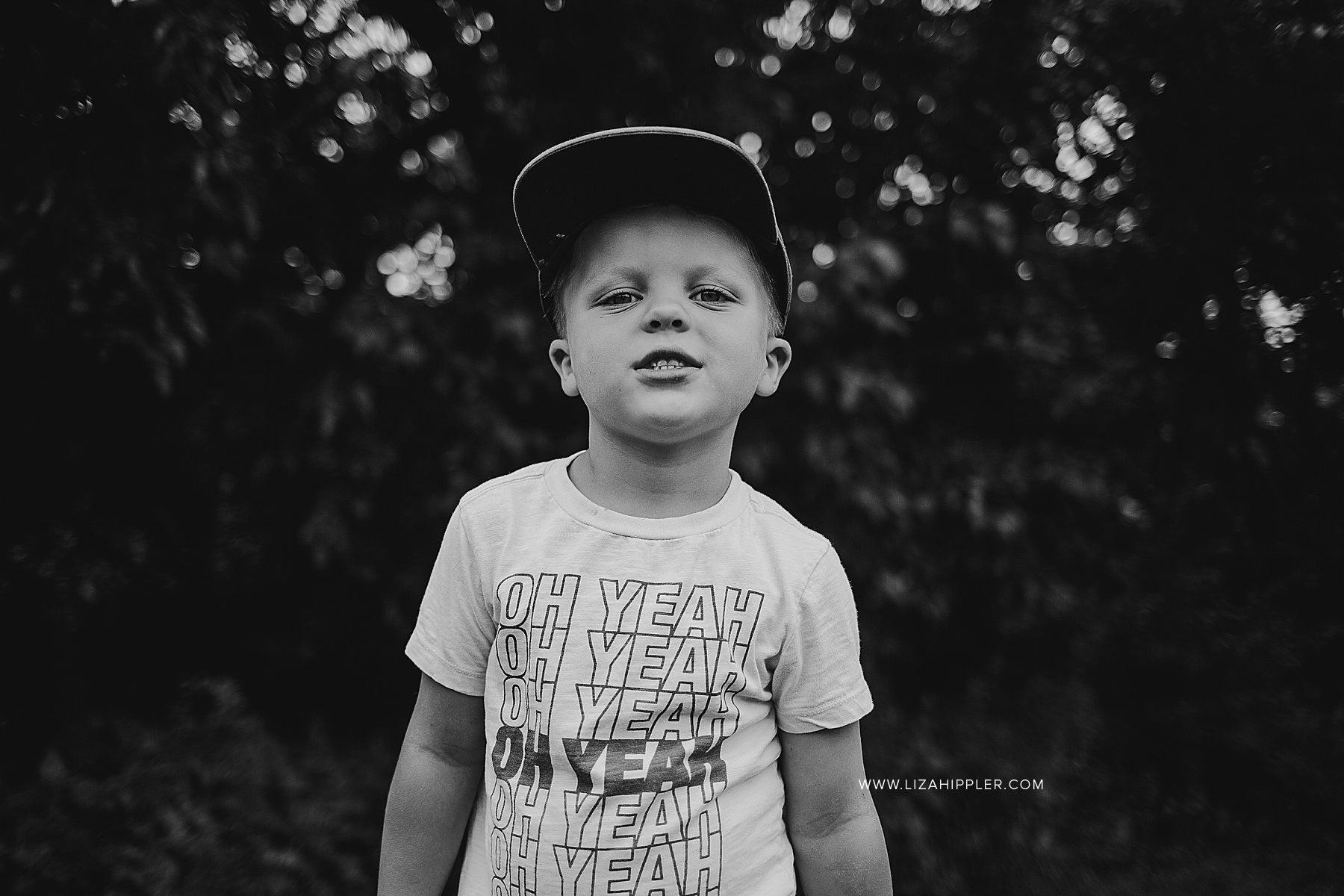 black and white image of young boy with baseball cap
