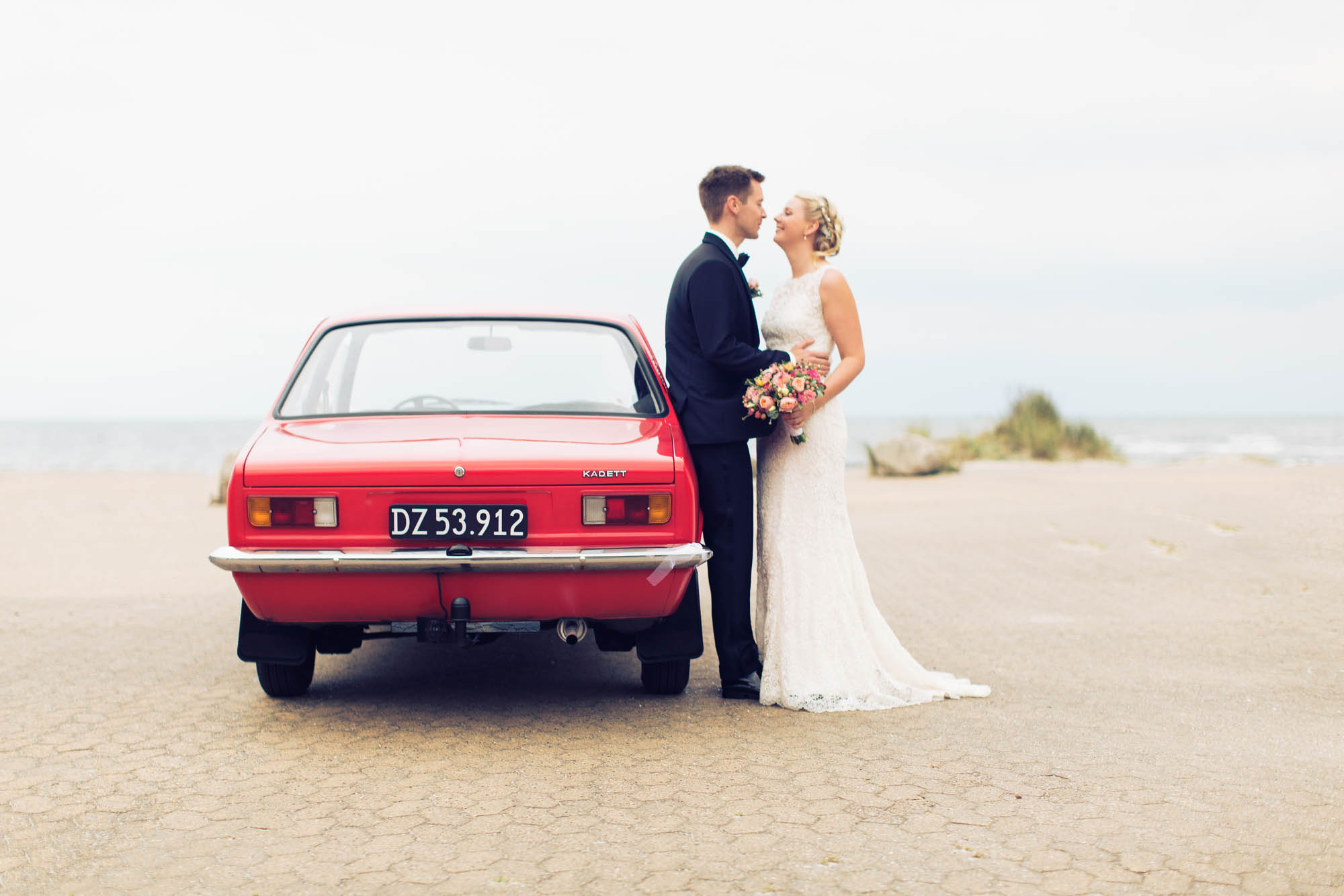 Brudepar fotograferet ved rød bil
