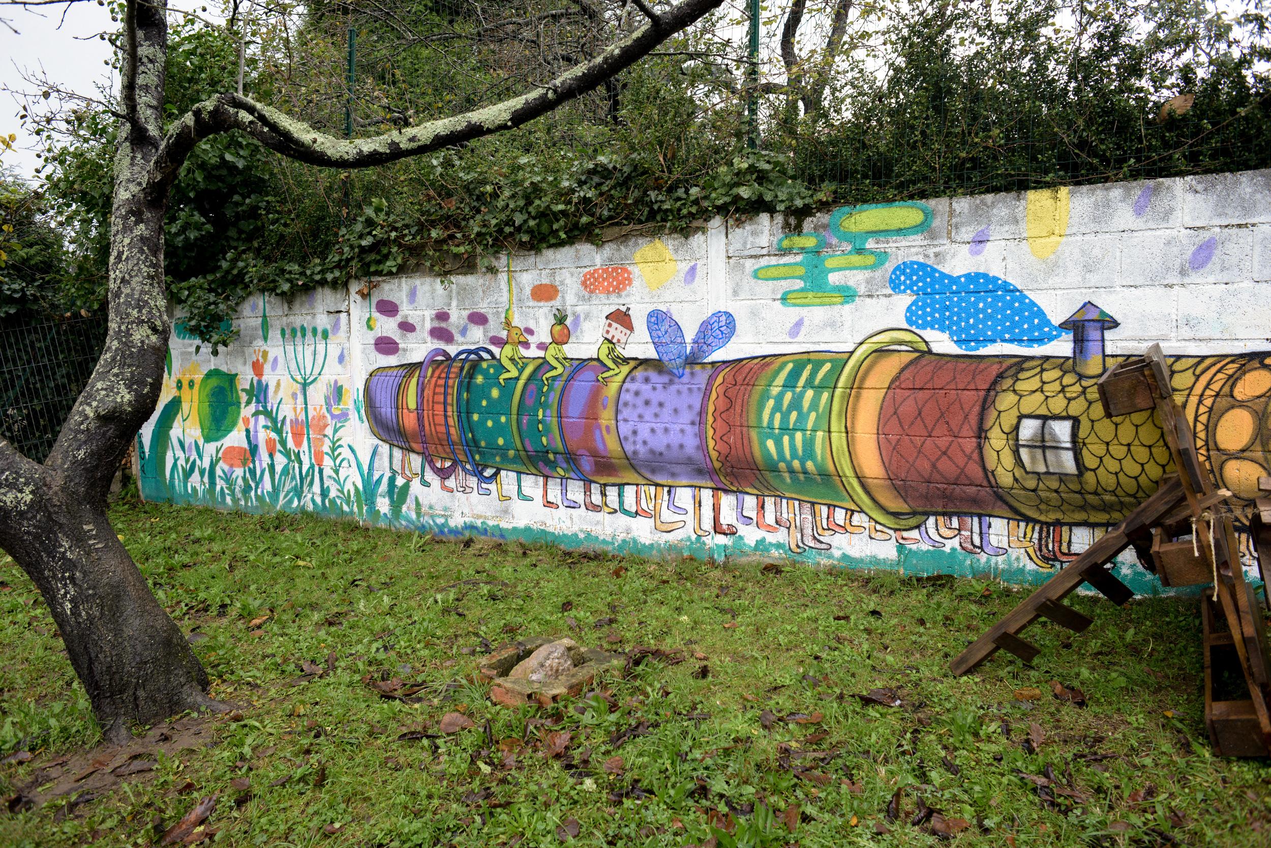 Un enorme graffiti multicolor alegra la vista de un muro de bloques en el patio de Andolina.