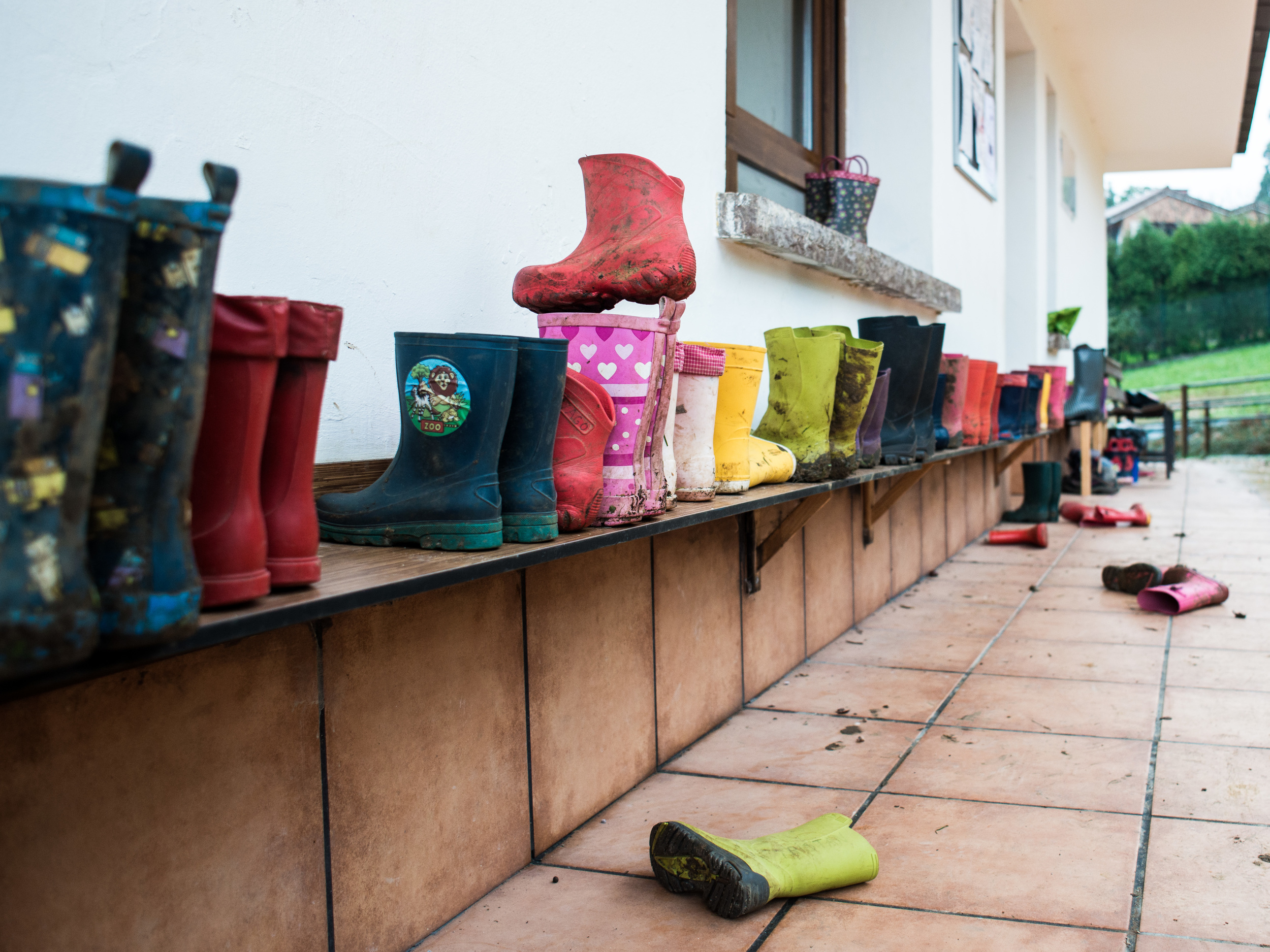 Las botas de agua a la entrada de Andolina, dispuestas en una estantería.
