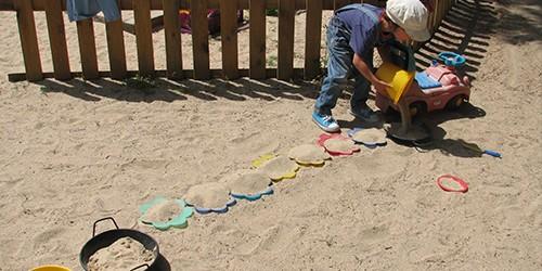 Una niña juega en el arenero rellenando moldes con arena.