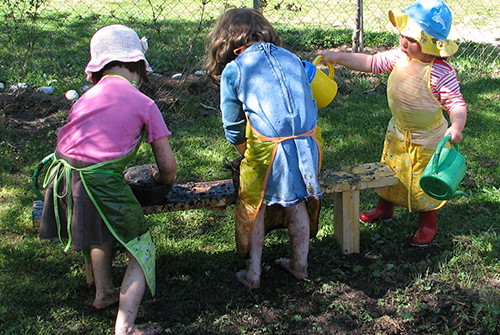 Niñas jugando afuera con la tierra, el agua, las plantas.