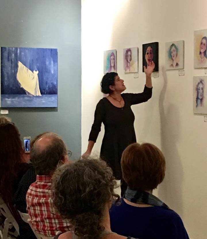 """Miki Berman explains her watercolor portraits (my painting """"Phenomenal Woman"""" on the gray wall behind her)."""