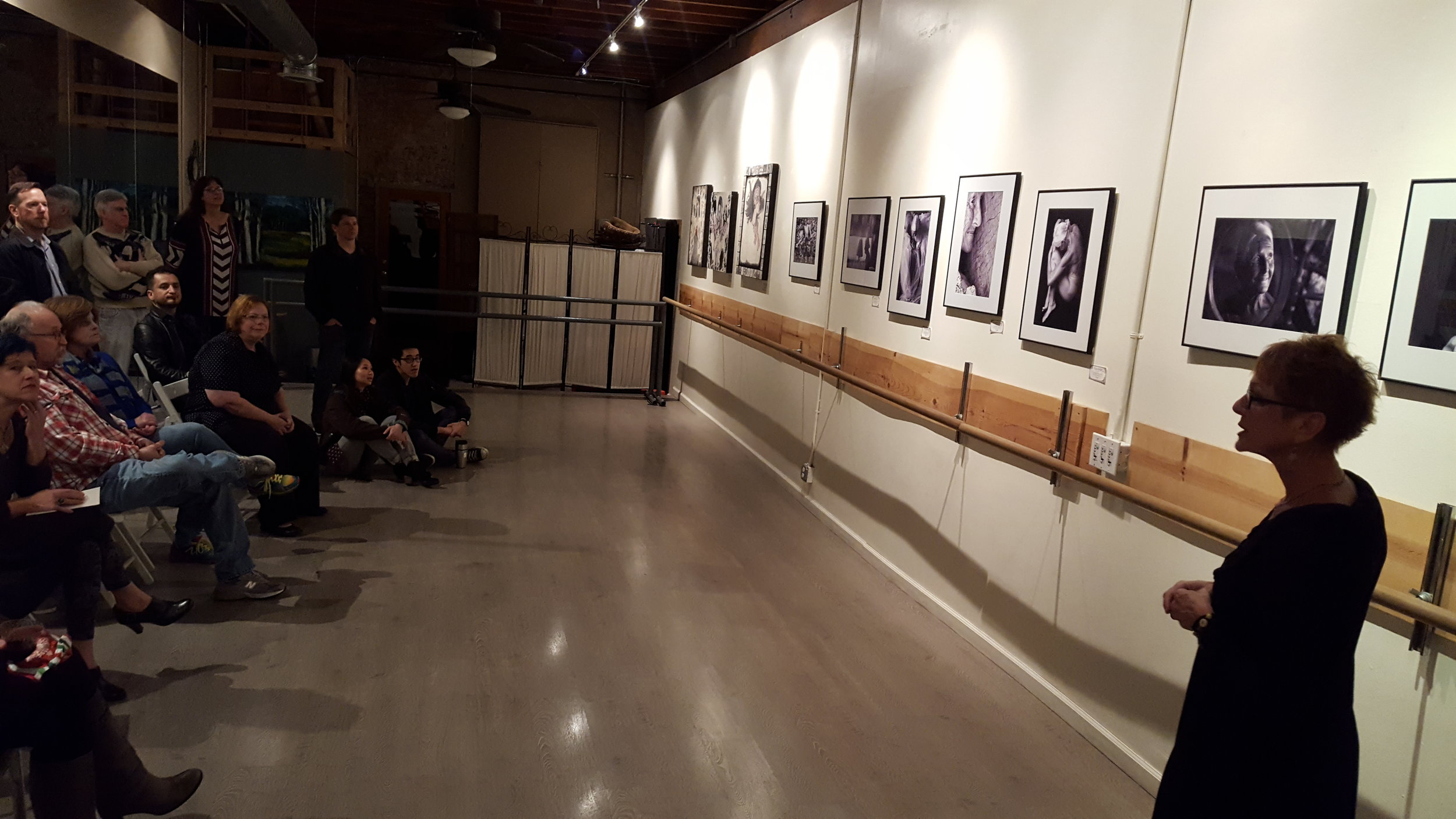 Mara Zaslove speaking in front of her black and white photographs.