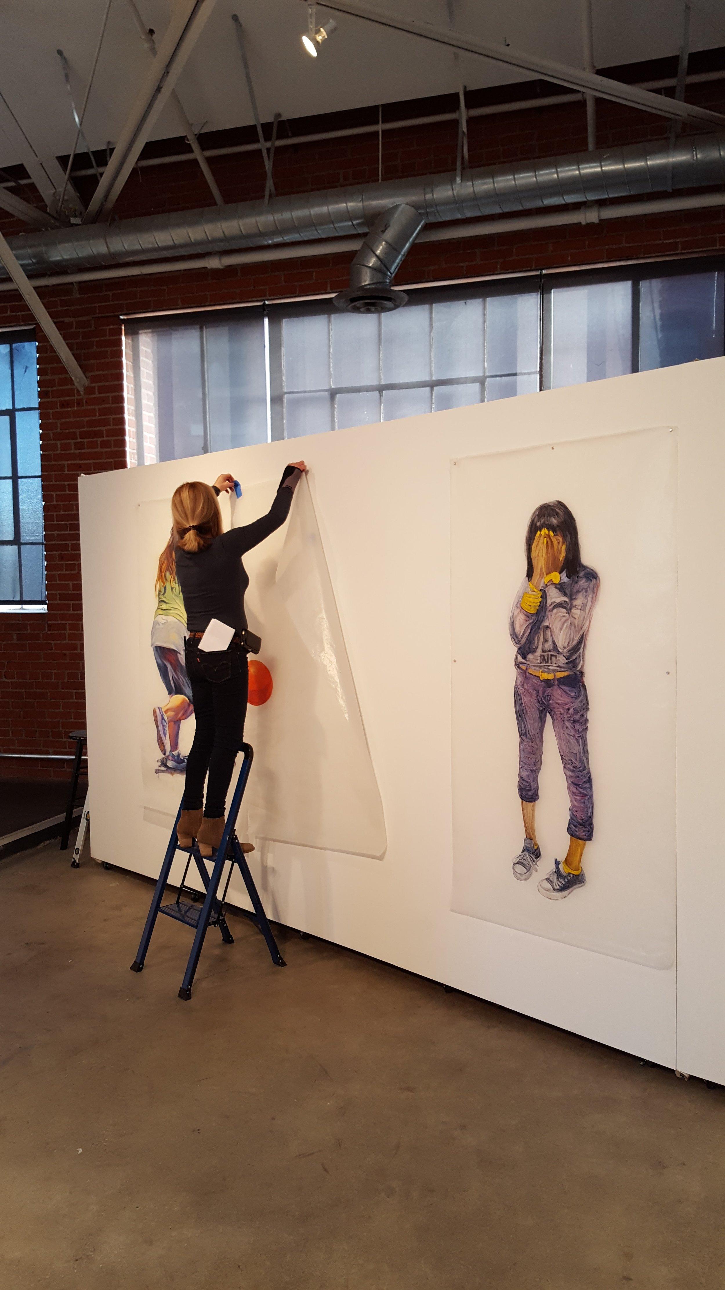 Deborah Decker hanging her paintings on glassene.|  Photo credit: C. Rasmussen.