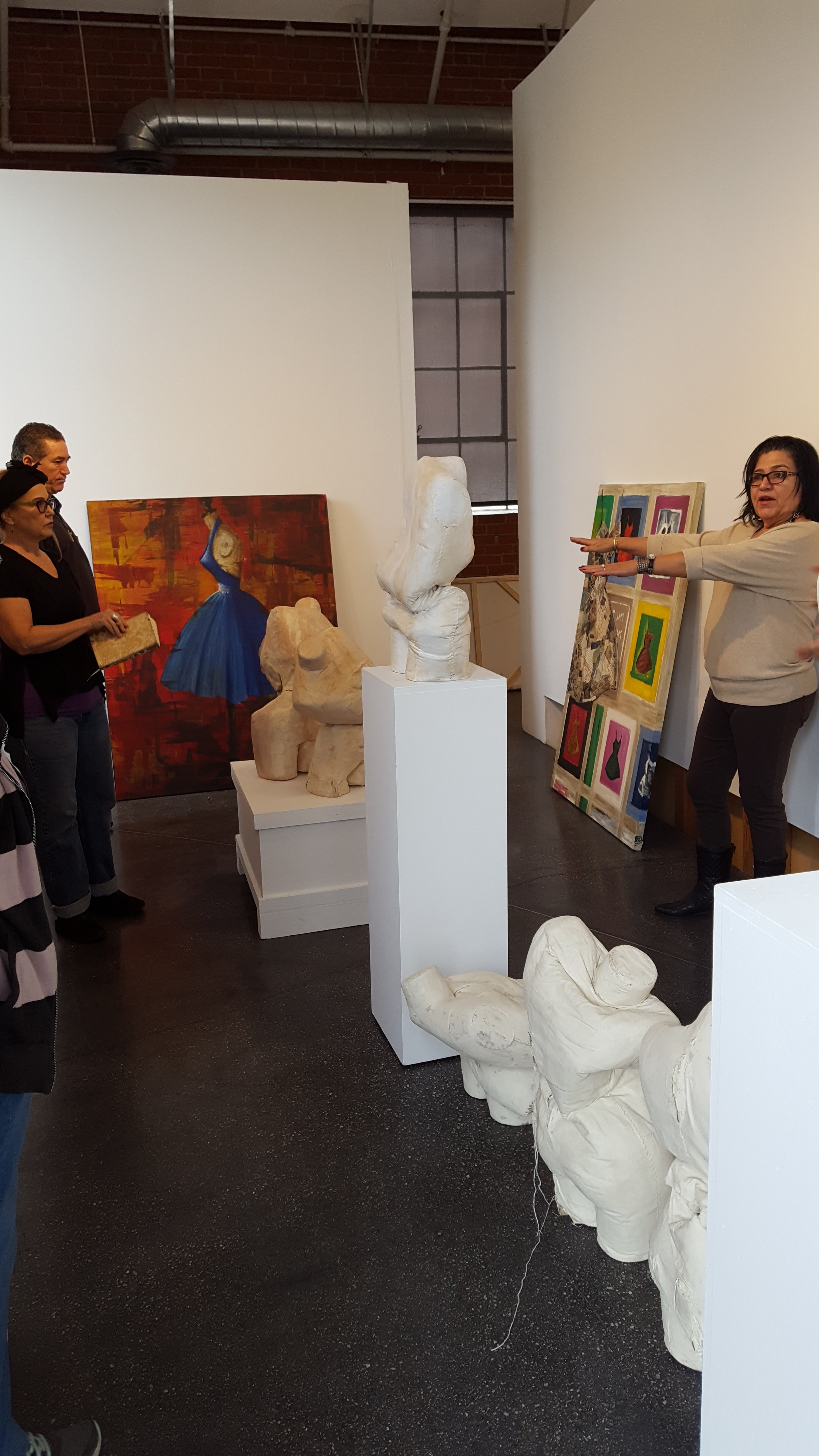 Curator Linda Vallejo (right) giving critique and instructing us where to put what. Artwork by Dawn Marie Forsyth (left with book).|  Photo credit: C. Rasmussen.