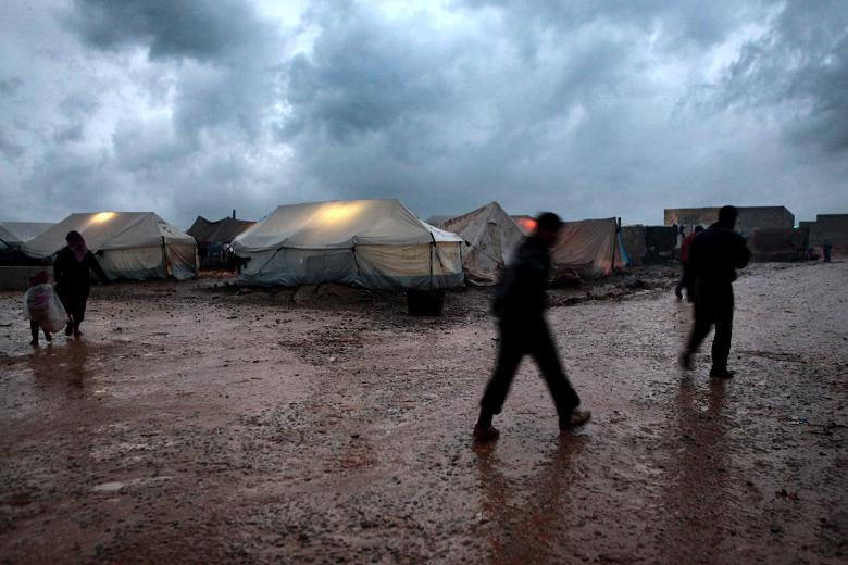Refugees in Atmeh camp trudge through the mud   Times photographer, Tom Pilston