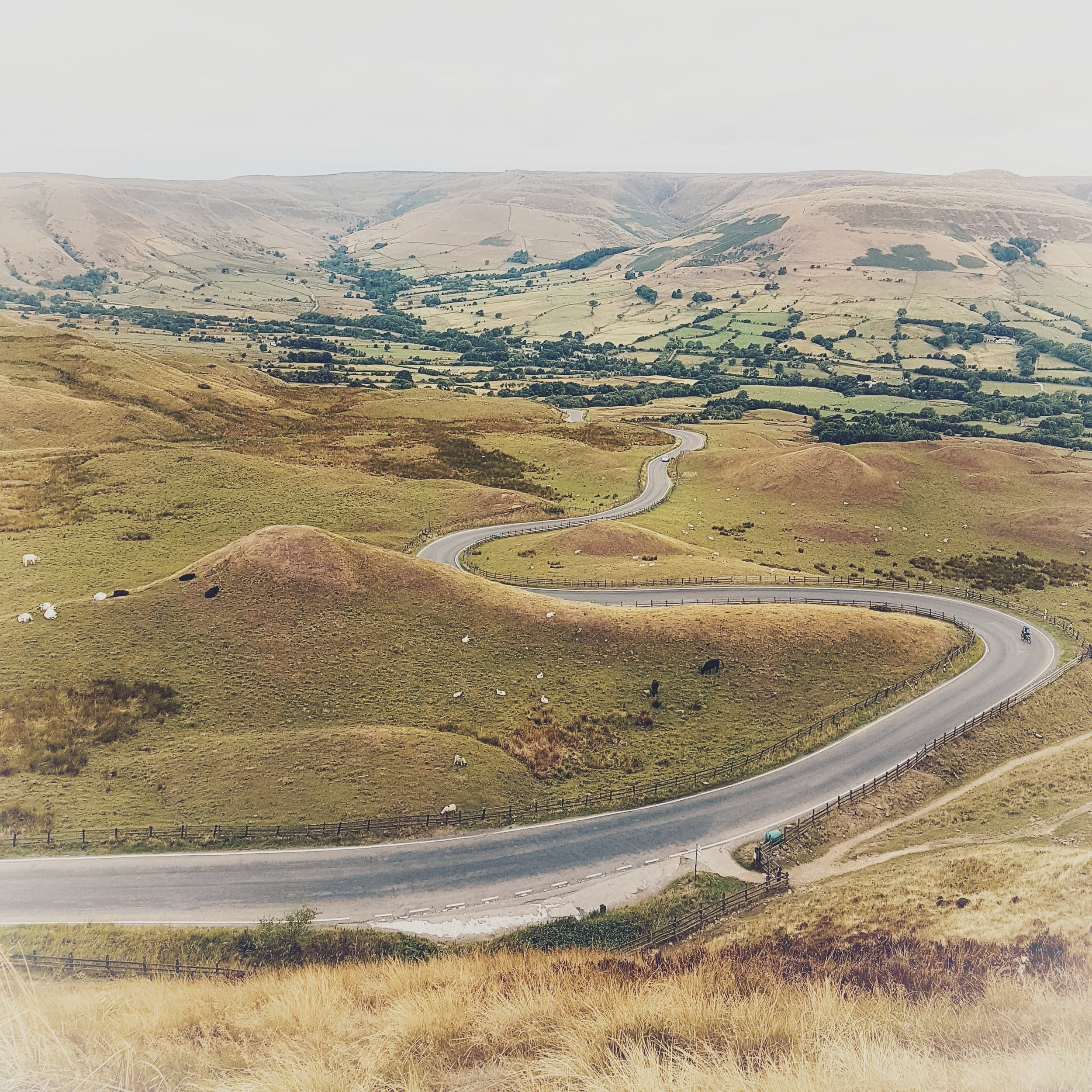 Here is a really popular viewpoint, on the hike up to the top of Mam Tor. This image shows the winding road into the village of Edale and in the far distance the  Kinder Plateau  and the start of the  Pennine Way , which forms part of the UK's trail network.  It is a impressive sight. Good to travel down, but harder to travel up. Especially if you decide to give it a go on your bike.