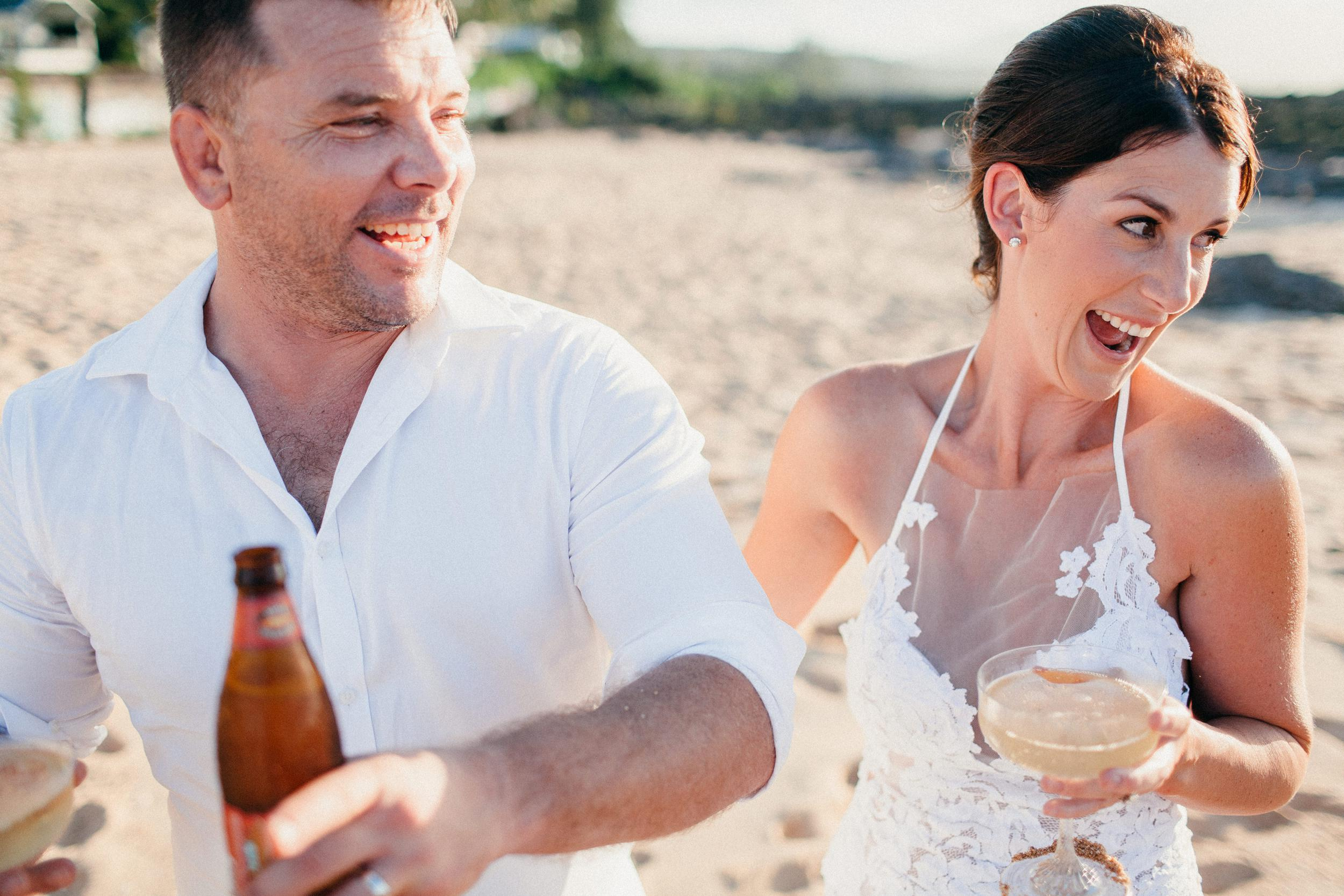 Anna & Ben share celebratory drinks after just getting married on the North Shore or Oahu
