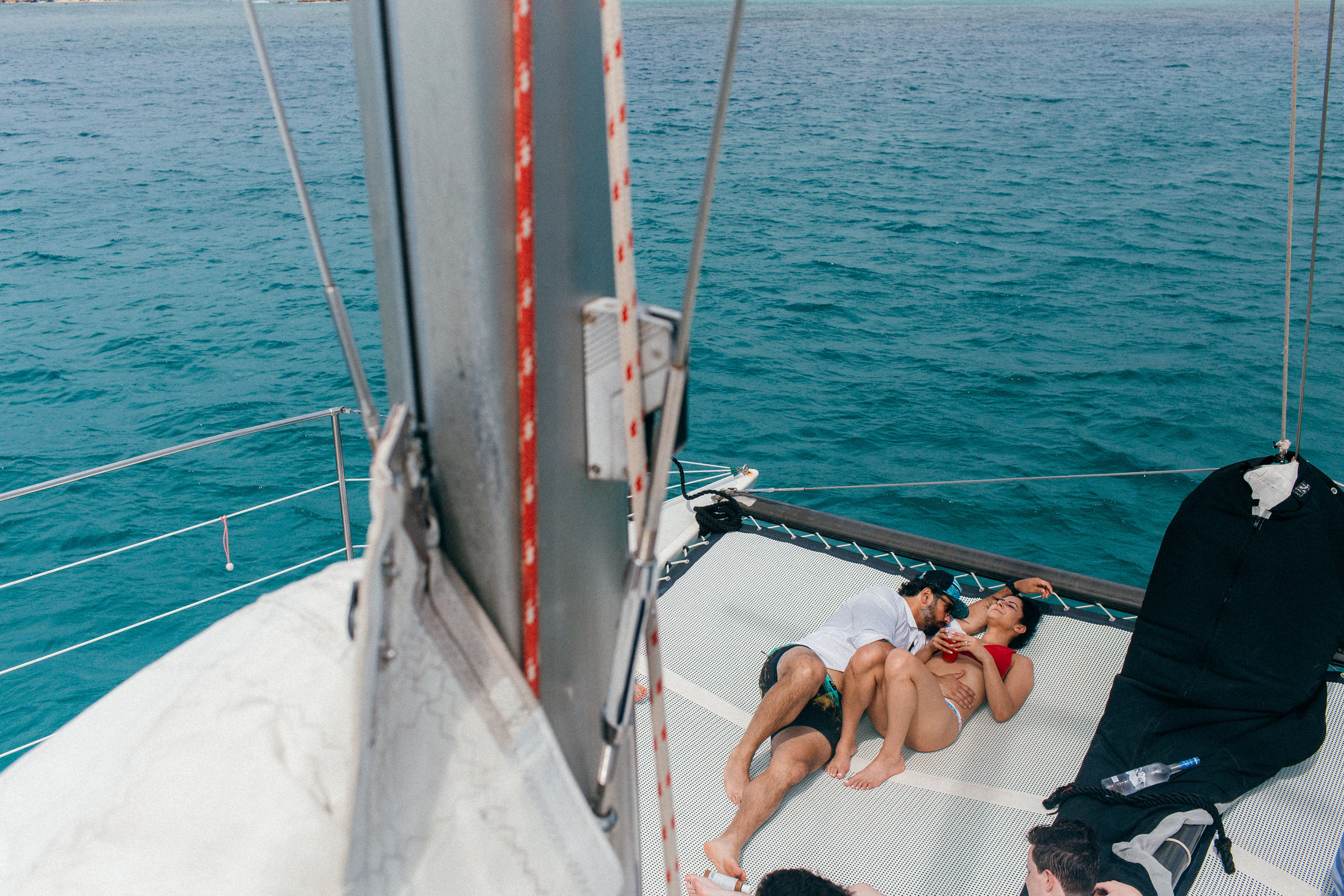 Victoria & Carlos on their rehearsal day with friends on a North Shore catamaran ride in Oahu, Hawaii