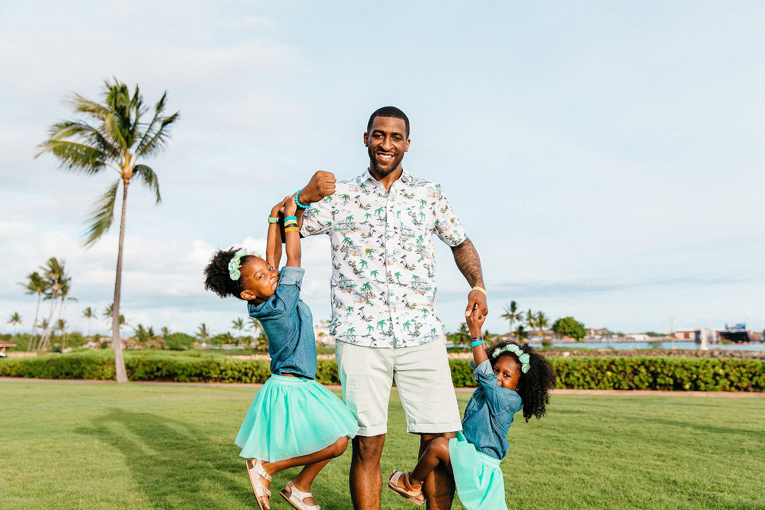 Dad and daughters together near palm trees and the beach at Ko Olina.