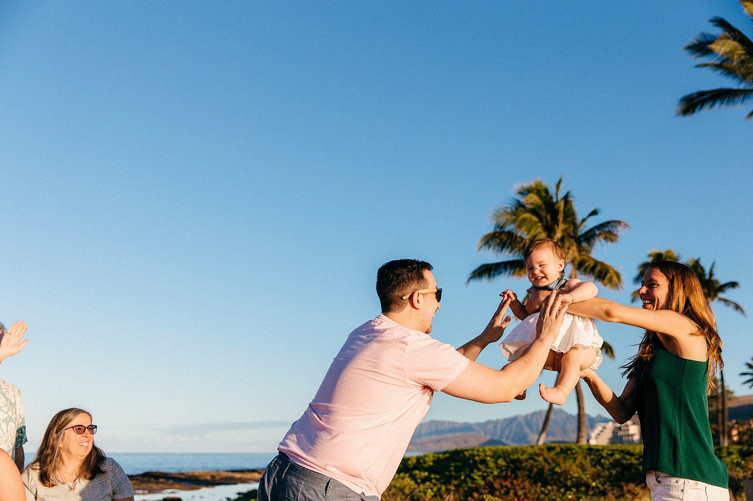 Mom and dad play with baby girl below palm trees, mountains, and the beach in Ko Olina.
