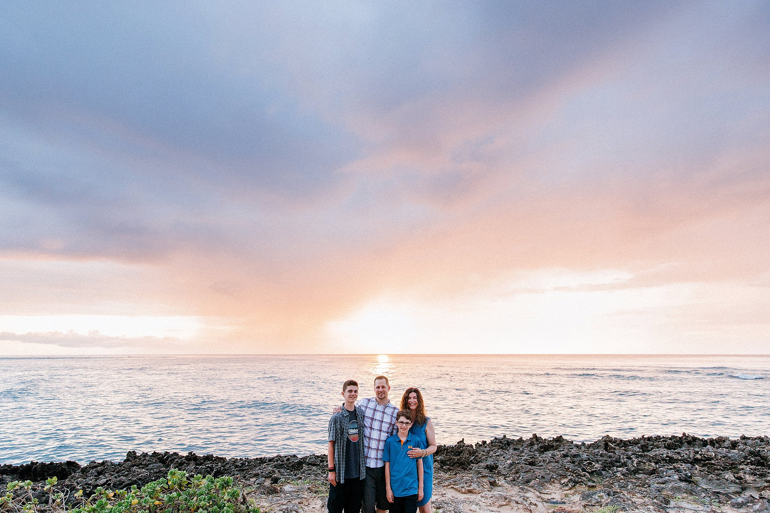 The Vittore family out on the cliffside point of Turtle Bay Resort at sunset time.