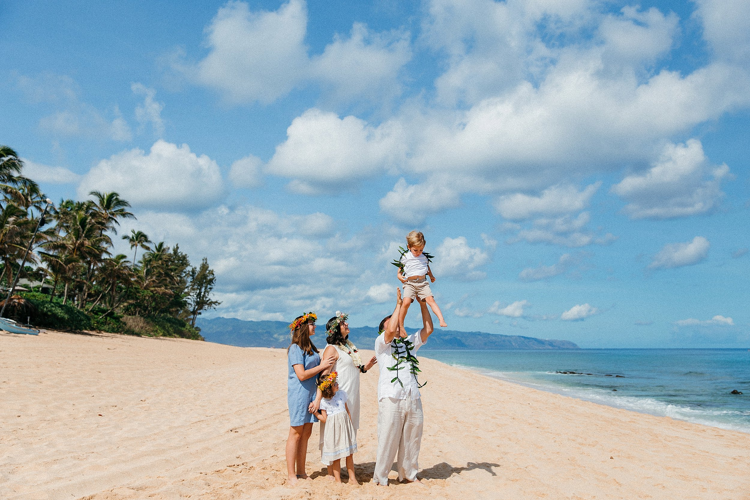 The Roukema Family playing together on the beach in front of the West Side mountain range on Oahu's North Shore.