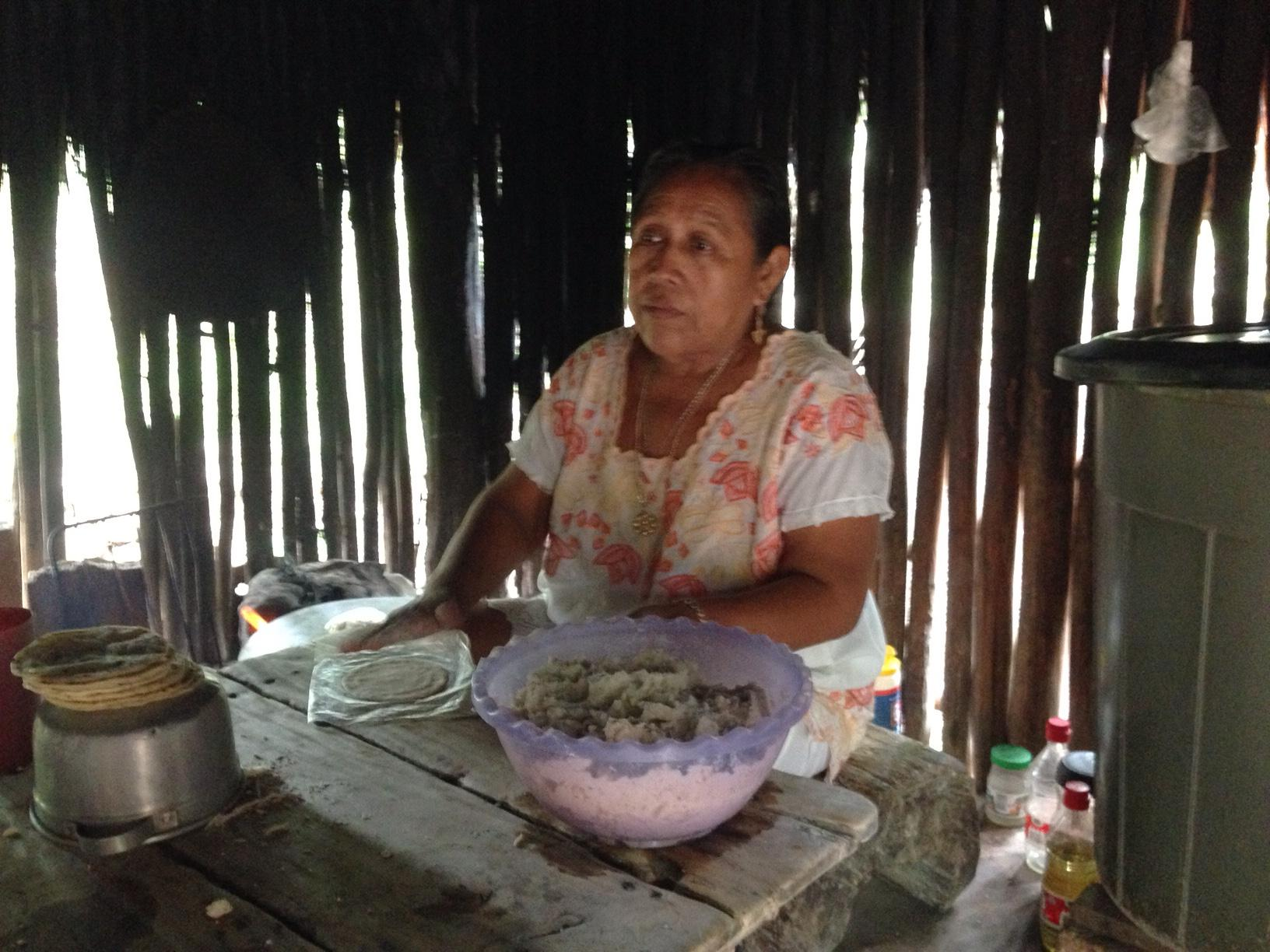 Francisca works in her kitchen to make tortillas from the ground corn meal. She cooks them on a very hot stone (on the ground just to her right) turning them with her fingers! Ouch!
