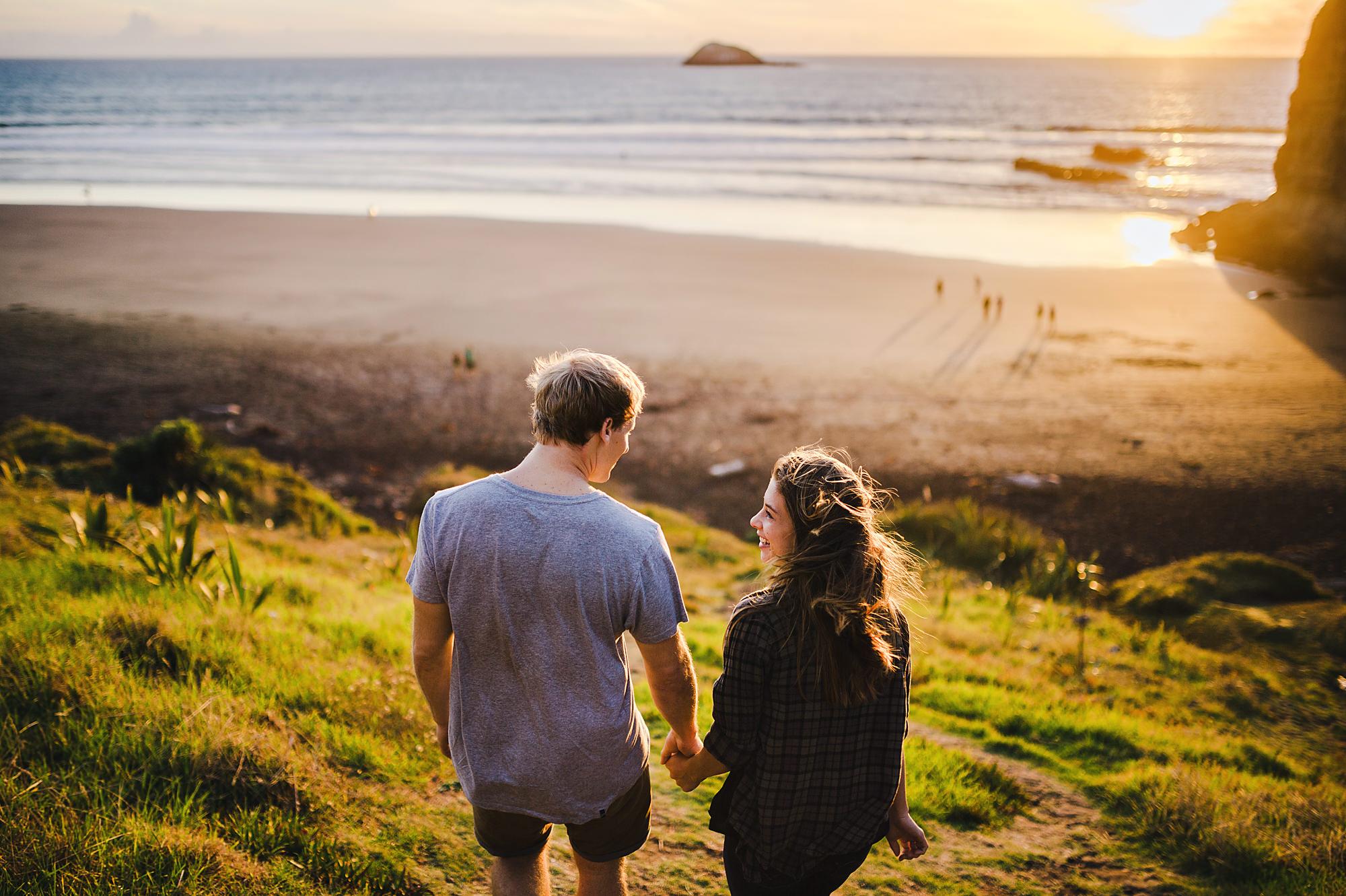 11 couple walking into sunset on beach muriwai.jpg
