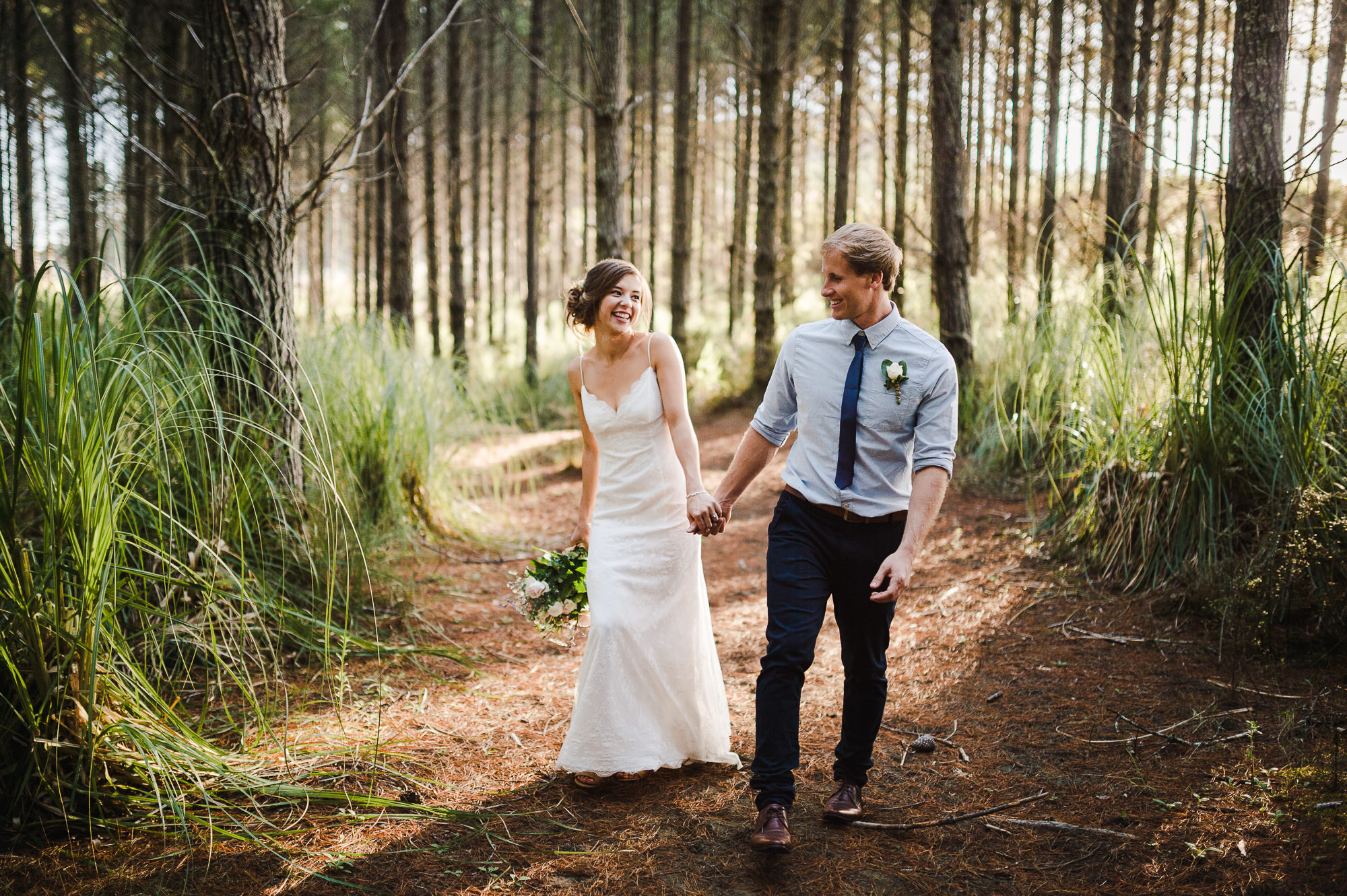 bride and groom walking through forest auckland wedding.jpg
