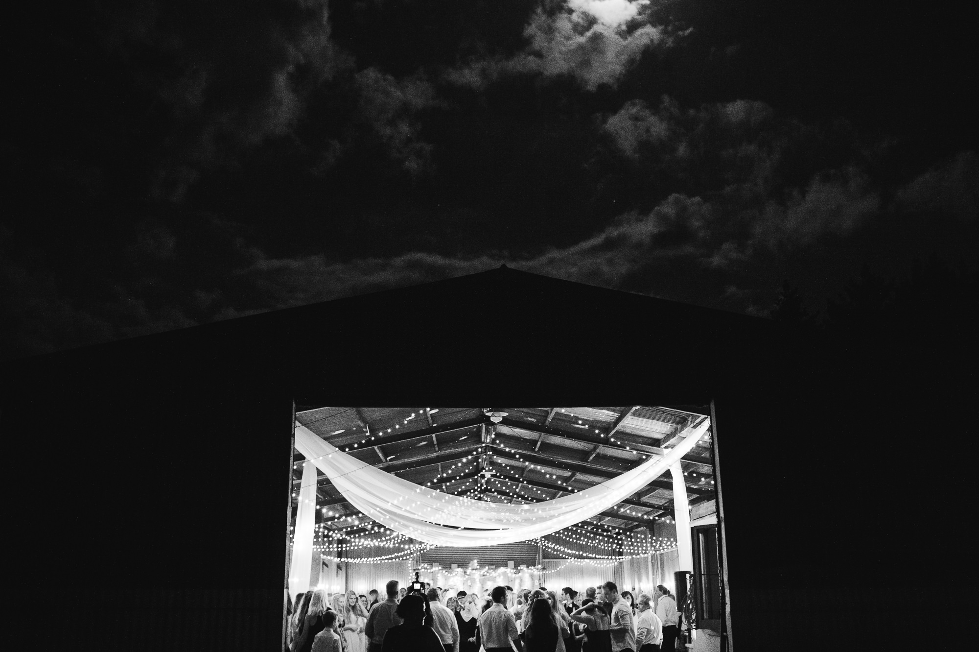wedding party beneath the moon in barn.jpg