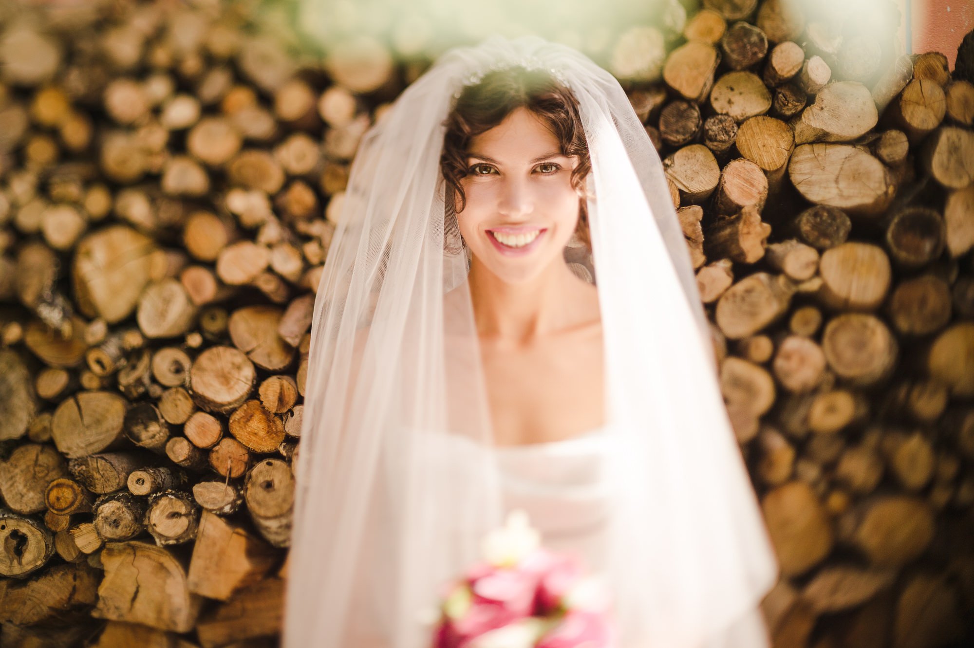 36 freelensed portrait of bride in front of logs auckland wedding.JPG