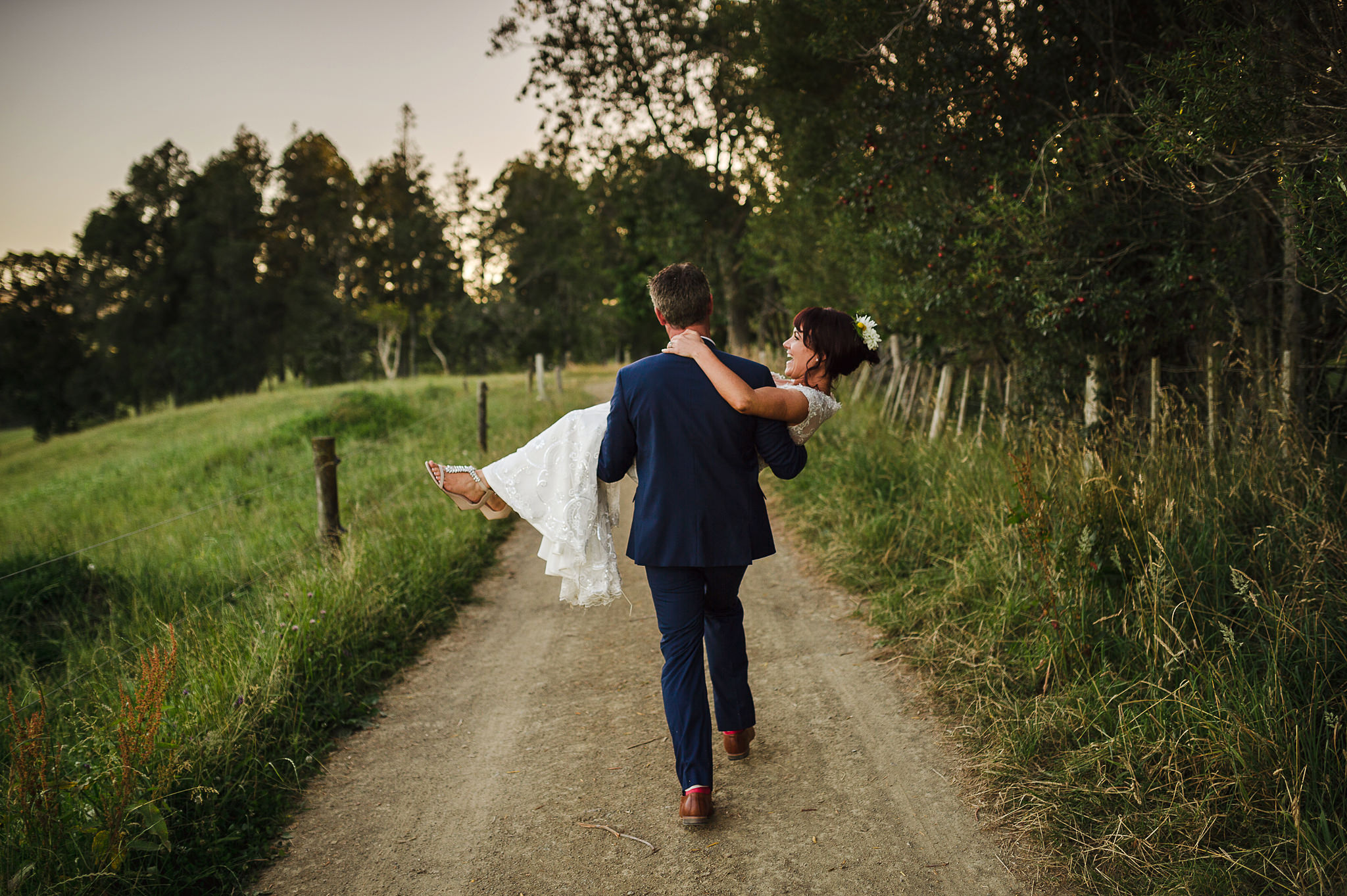 37 raglan wedding spontaneous moment groom carrying bride through countryside.JPG