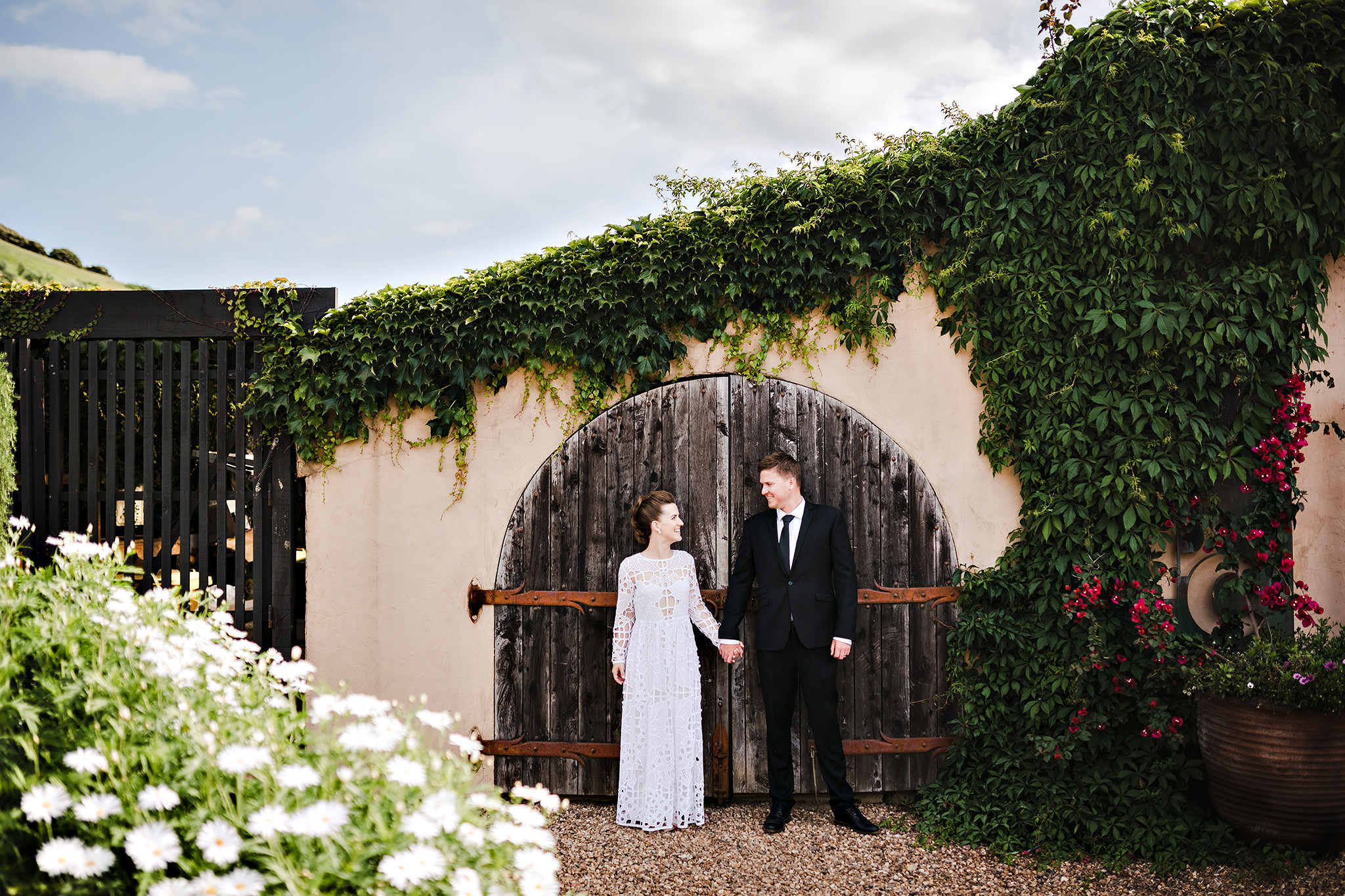 39 waiheke island bride with rad dress in front of barn doors.JPG