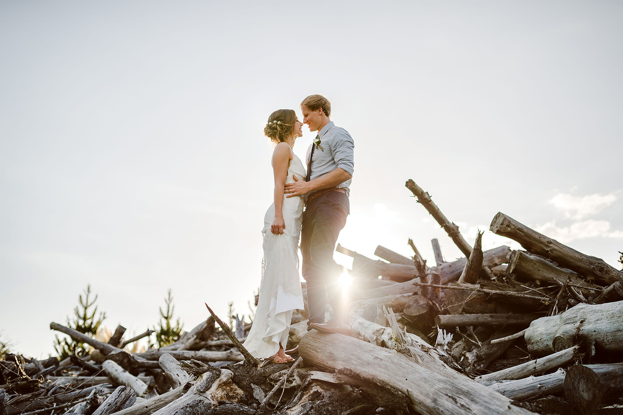 61A Muriwai Woodhill Kumeu wedding Bride and groom on pile of logs.JPG