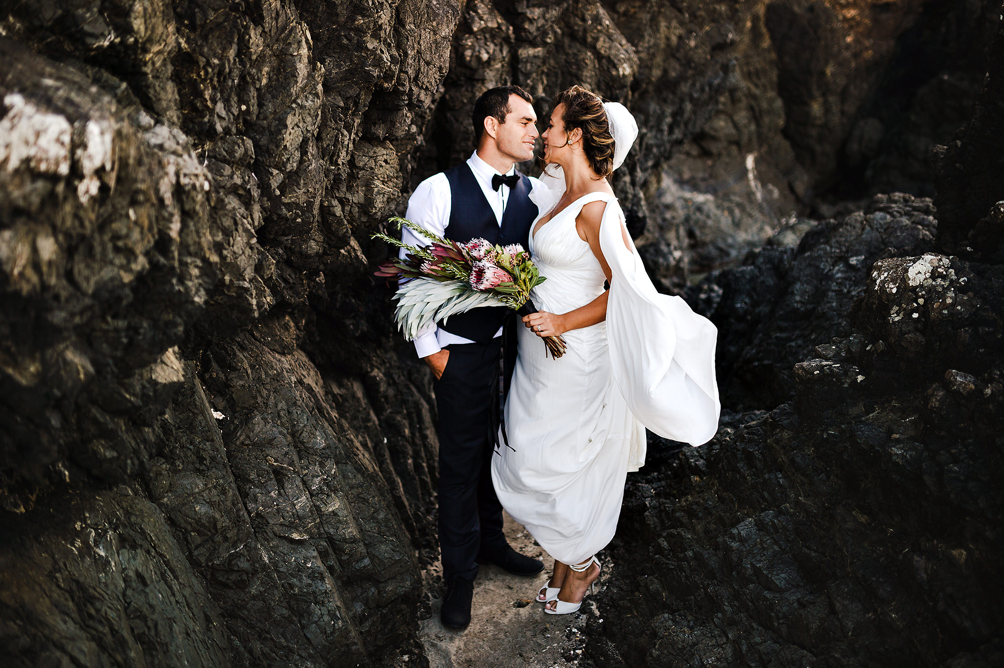 65 whananaki wedding bride and groom amongst rocks.JPG
