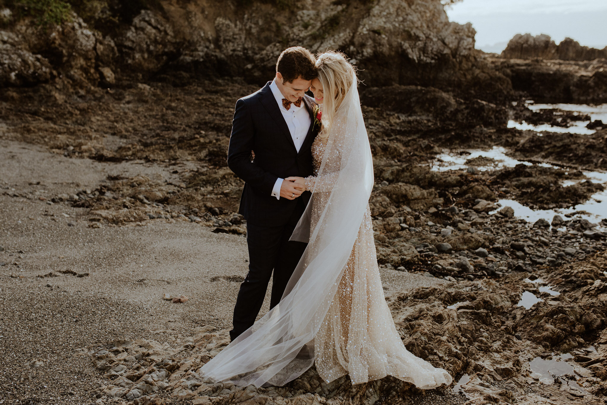 Bride and groom wedding photos on rocky cove, Waiheke Island