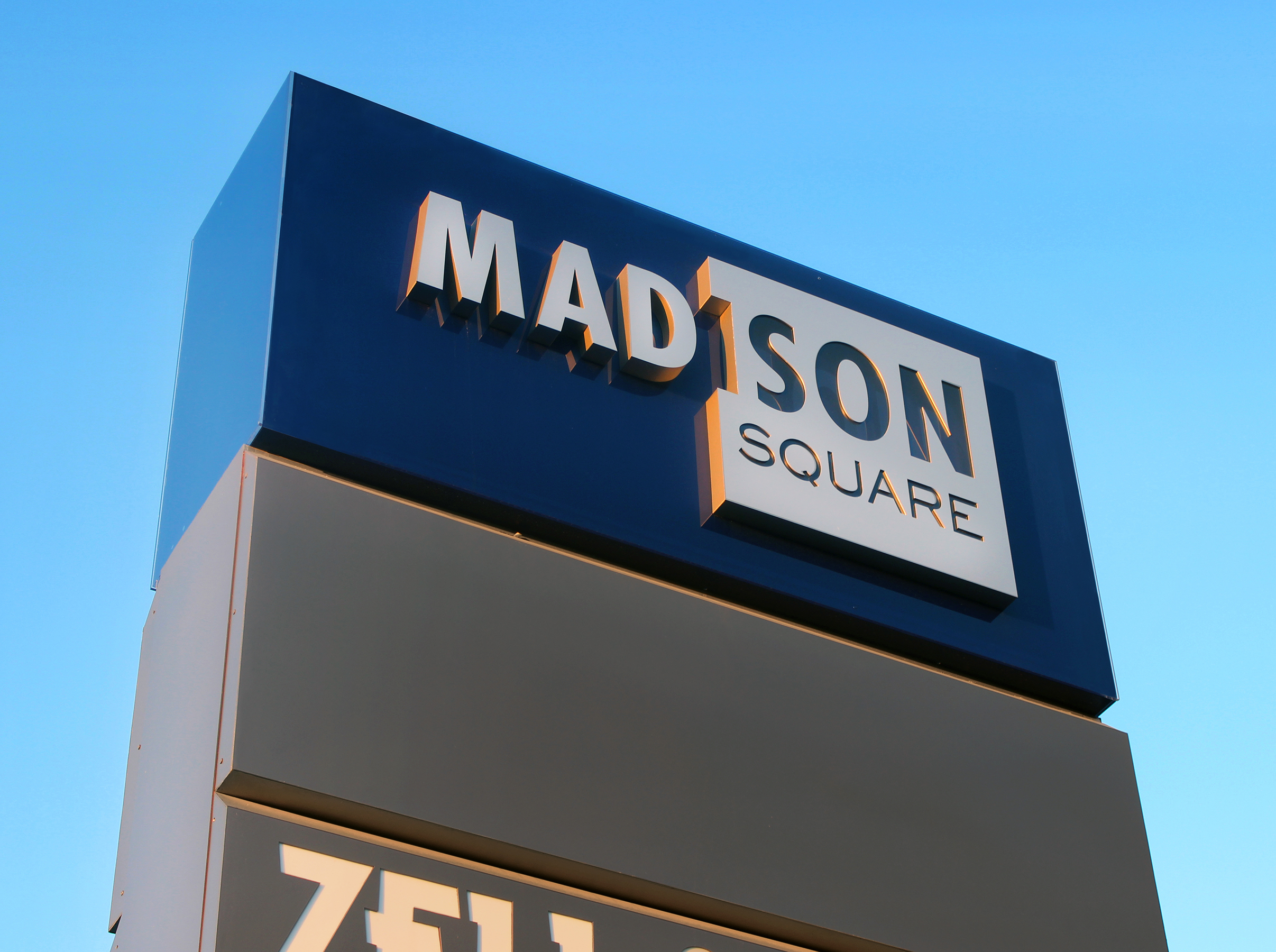 The sign's branding element is constructed of blue acrylic and aluminum fabricated letters/logo.