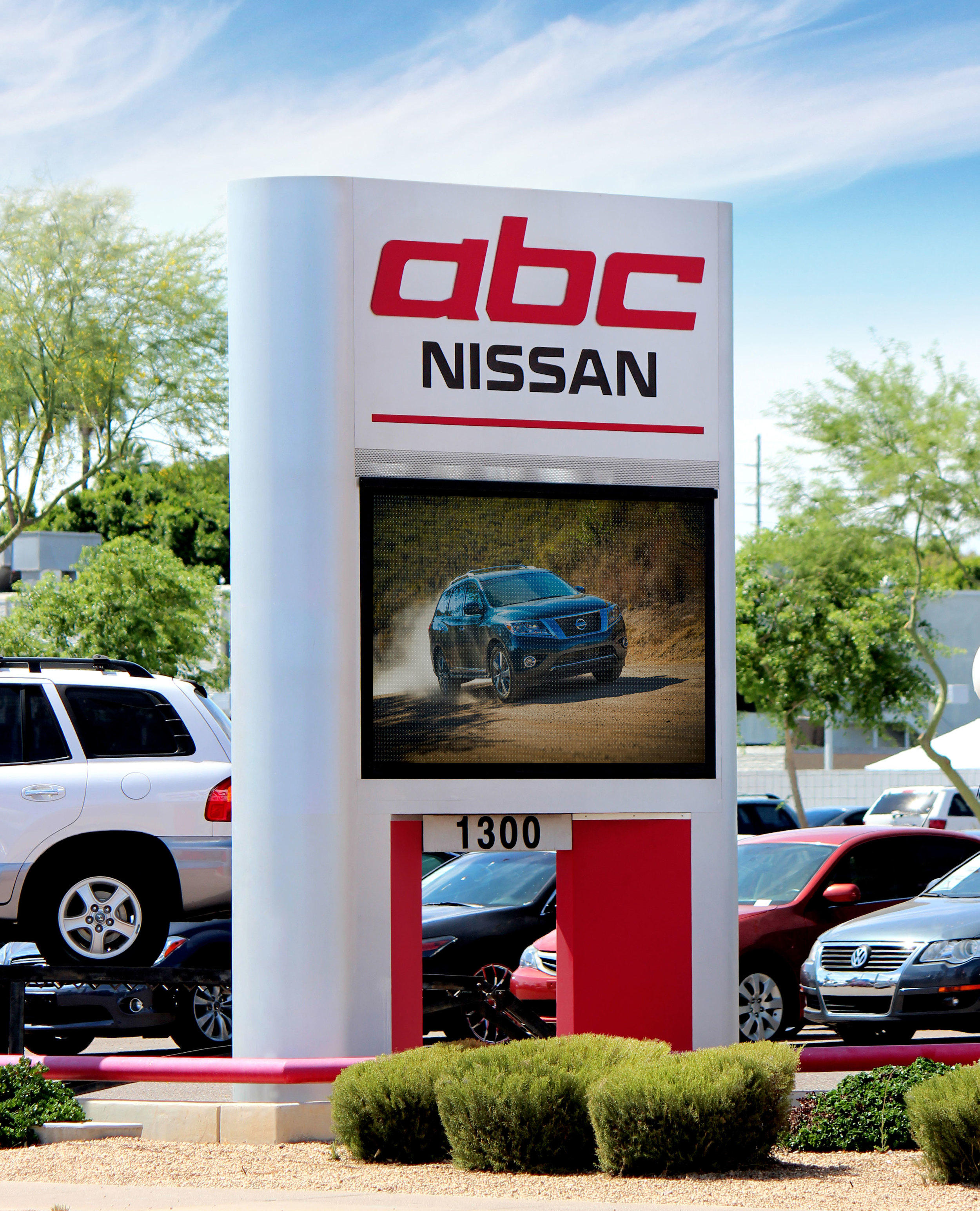 A Nissan freestanding double sided electronic message center ground sign displays various full color messages.